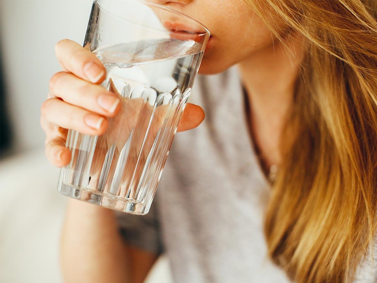 Donna beve bicchiere di acqua ottenuta da depuratore